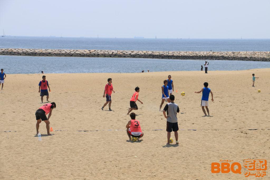 芦屋浜BBQコーナー隣接の潮芦屋ビーチバレーコートでサッカーをする人